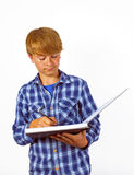 Smart boy is writing into a book Royalty Free Stock Image