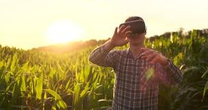 Smart bruka med IoT, futuristiskt åkerbrukt begrepp: Bonden bär VR- eller AR-exponeringsglas, medan övervaka nederbörd stock video