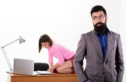 Smart and brutal. Brutal hipster with sexy woman working in office background. Brutal businessman and coworker on. Smart and brutal. Brutal hipster with sexy stock images