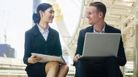 The smart business caucasian man and secretary asia women sit Royalty Free Stock Photo