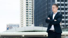 Smart business confident man stand at the outdoor public space. With modern building background Stock Image