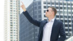 Smart business confident man stand at the outdoor public space w. The smart business confident man stand at outdoor public space with modern building Royalty Free Stock Image