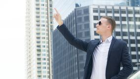 Smart business confident man stand at the outdoor public space w. The smart business confident man stand at  outdoor public space with modern building Royalty Free Stock Images