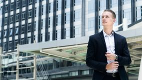 Smart business confident man stand at the outdoor public space w. The smart business confident man stand at the outdoor public space with modern building Royalty Free Stock Photography