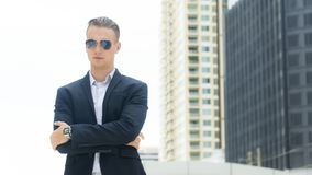 Smart business confident man stand at the outdoor public space w. The smart business confident man stand at outdoor public space with modern building Royalty Free Stock Photo