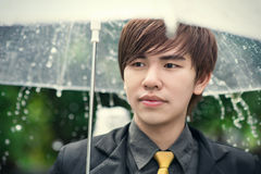 Smart business man holding umbrella among the rain Royalty Free Stock Photography