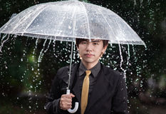 Smart business man holding umbrella among the rain Royalty Free Stock Photos