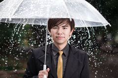Smart business man holding umbrella among the rain Stock Photos