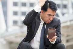 Smart business man is looking his mobile phone and check his rea. Diness and make himself has good looking to meet partner Stock Image