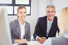 Smart business people sitting at desk in office Stock Images
