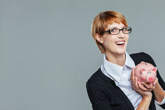 Smart business woman happy with her piggy bank Royalty Free Stock Image