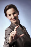 Smart business woman holding key between fingers Stock Image