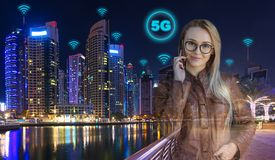 Smart business woman with modern city in background at night using 5G speed wireless connection to call with smartphone stock image