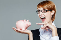 Smart business woman pointing finger to her satisfied piggy bank Royalty Free Stock Photos