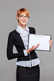 Smart business woman pointing at her clipboard and smiling Royalty Free Stock Images