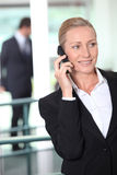 Smart business woman. Using a cell phone in an office environment stock photos