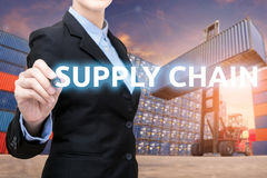 Smart business woman is writing Supply chain word. With forklift lifting cargo container and cargo containers stack in background for global transportation Royalty Free Stock Photo