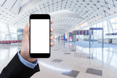 Smart Business women showing smartphone with blank white screen. And blurred international airport in background. Elegant Design with copy space for technology Stock Images