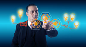 Smart Businessman Activating Solar Energy Buttons. Smart businessman with focused gaze is activating solar icons for electric power generation via a touch screen Stock Photo