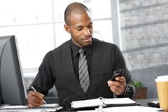 Smart businessman busy working. Portrait of smart businessman busy working at desk, using mobile phone, taking notes, concentrating Stock Image