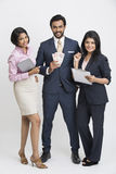 Smart  businessman holding money standing with his colleague. Smiling businessman holding money standing with his colleagues on white background Royalty Free Stock Photography