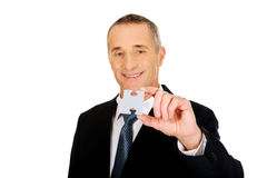 Smart businessman holding a puzzle stock photography
