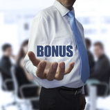 Smart businessman holding the word bonus. In front of a business team stock images