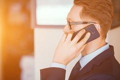 Smart businessman talking on the phone in sunny office. Businessman Talking On Phone . Standing Middle Sunny Office. Wearing Black Suit With Tie. Business In royalty free stock image