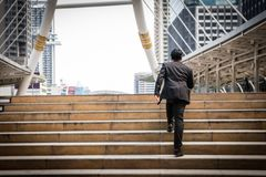 Smart Businessman is walking on the steps and heading to his goa. L. Competition between big and small enterprise.  Starting business with confident Royalty Free Stock Images