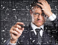 A smart businessman writing imaginary text over grey Stock Images