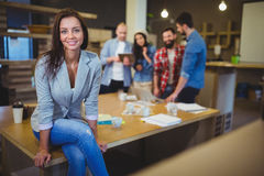 Smart businesswoman sitting on table in office Stock Image