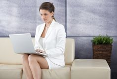 Smart businesswoman on sofa with laptop Royalty Free Stock Photos
