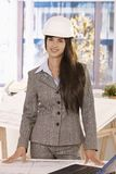 Smart businesswoman wearing hardhat smiling Royalty Free Stock Images