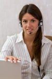 Smart busineswoman med en hörlurar med mikrofon och en bärbar dator Fotografering för Bildbyråer