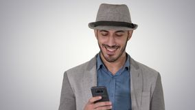 Smart casual arabian man using smartphone while walking on gradient background. Close up. Smart casual arabian man using smartphone while walking on gradient stock footage