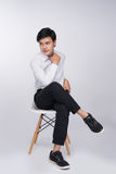 Smart casual asian man seated on chair, posing while looking awa Stock Images