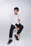 Smart casual asian man seated on chair, posing while looking awa Stock Image