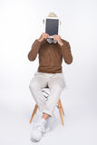 Smart casual asian man seated on chair, showing digital tablet s Royalty Free Stock Image