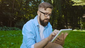Smart casual man with digital tablet outdoors, close up. Modern remote work concept. Smart casual man with digital tablet outdoors, close up. Focus on finger stock video