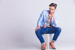 Smart casual man seated on box, wearing glasses Stock Image