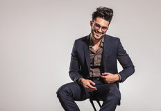 Smart casual man in suit sitting on chair and laughing Stock Images