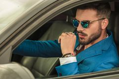 Smart casual man with sunglasses and blue suit driving car. Smart casual man with sunglasses and blue suit driving his grey car, portrait picture stock image