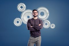 A smart casual man wears glasses and stands in a front view with several large spur gears behind him. royalty free stock photo