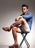 Smart casual young man sitting on a stool Royalty Free Stock Photography