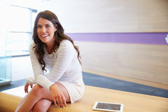 Smart casually dressed young woman sits looking to camera Stock Photo