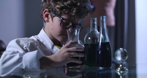 Smart Caucasian boy in eyeglasses and lab coat looking at flasks with liquids. Young teenage genius working on his