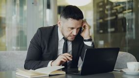 Concentrated caucasian businessman sitting, talking on his smartphone and writing down business information in his. Smart Caucasian businessman sitting, talking stock footage