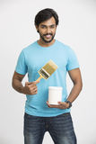 Smart cheerful man holding a paint brush and a paint. Smart man holding a paint brush and a paint bucket, looking at camera Stock Images