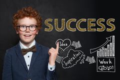 Smart child boy with hand drawing sketch and success text. Business idea and success concept.  royalty free stock photography