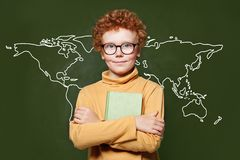 Smart child boy with map of Earth on green chalkboard. Environmental protection concept.  royalty free stock photography